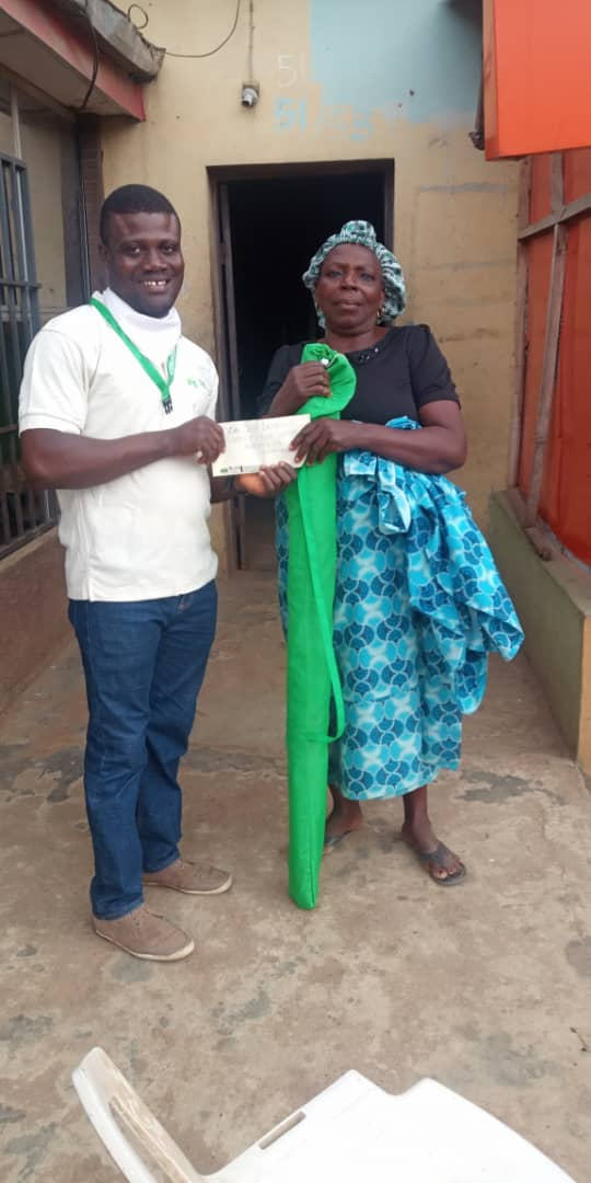 Caring for the elderly... Lotus Initiative Program Manager Presenting Cash Gift to an Elder.