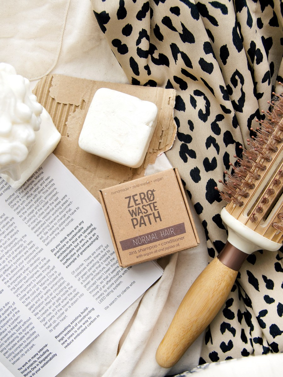 Flat lay image of a shampoo bar, with box. Hair brush to the right of shampoo bar. Leopard print material in background on the right and page magazine to the left.