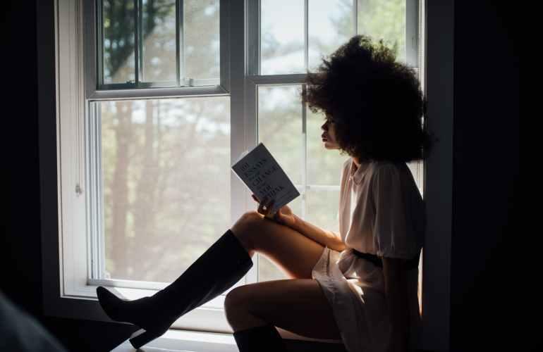 woman sitting on window reading book