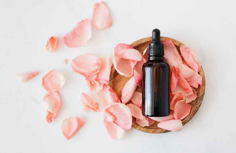 composition of cosmetic bottle with pink rose petals and wooden plate