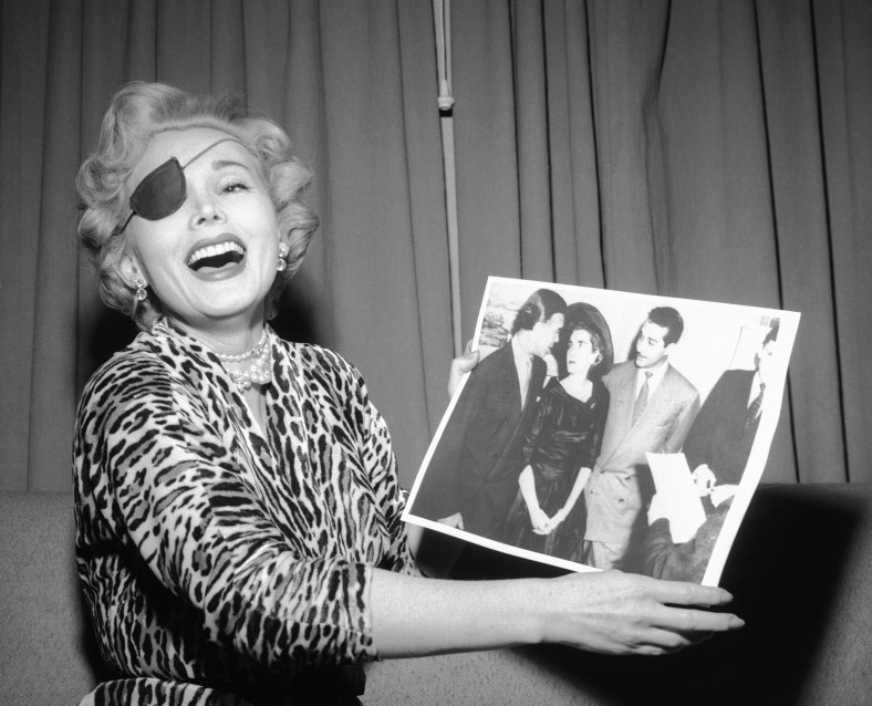 "03 Jan 1954, Las Vegas, Nevada, USA --- 1/3/1954-Las Vegas, NV: ""Look how unhappy they both look!"" Zsa Zsa Gabor laughs as she is handed a United Press Telephoto of the Porfirio Rubirosa and Barbara Hutton wedding shortly after the ceremony on Dec.30 in New York. In her suite in the Hotel Last Frontier the Hungarian beauty sniffed that she was ""very, very happy"" that Rubirosa got married because now he can pay her the $5,600 hotel bill he owes her. Zsa Zsa has already explained that she's wearing a patch to cover a black eye she says Rubirosa gave her. --- Image by © Bettmann/CORBIS"