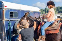 Darcey Lima (left) helping Raina May(right) onto Annie the mule.