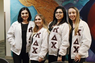 """Sisters of Kappa Delta Chi pose for a photo in their letters. Sweatshirts, shirts and jackets that feature an organization's name in the Greek alphabet are referred to as """"letters."""" Letters are a way for individual members to showing spirit and pride for their organizations."""