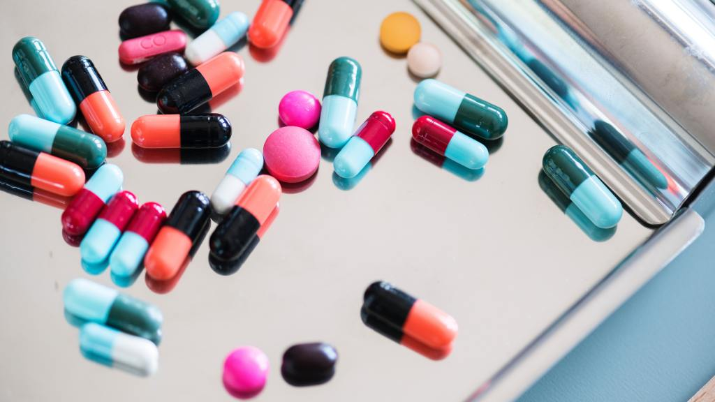 A pile of colorful pills spilled across a silver tray.