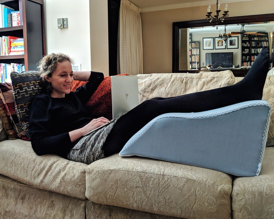 Alexa reclines on the couch with her legs elevated on a Lounge Doctor Leg Rest pillow.
