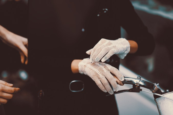Person wearing lace gloves while holding onto a bicycle