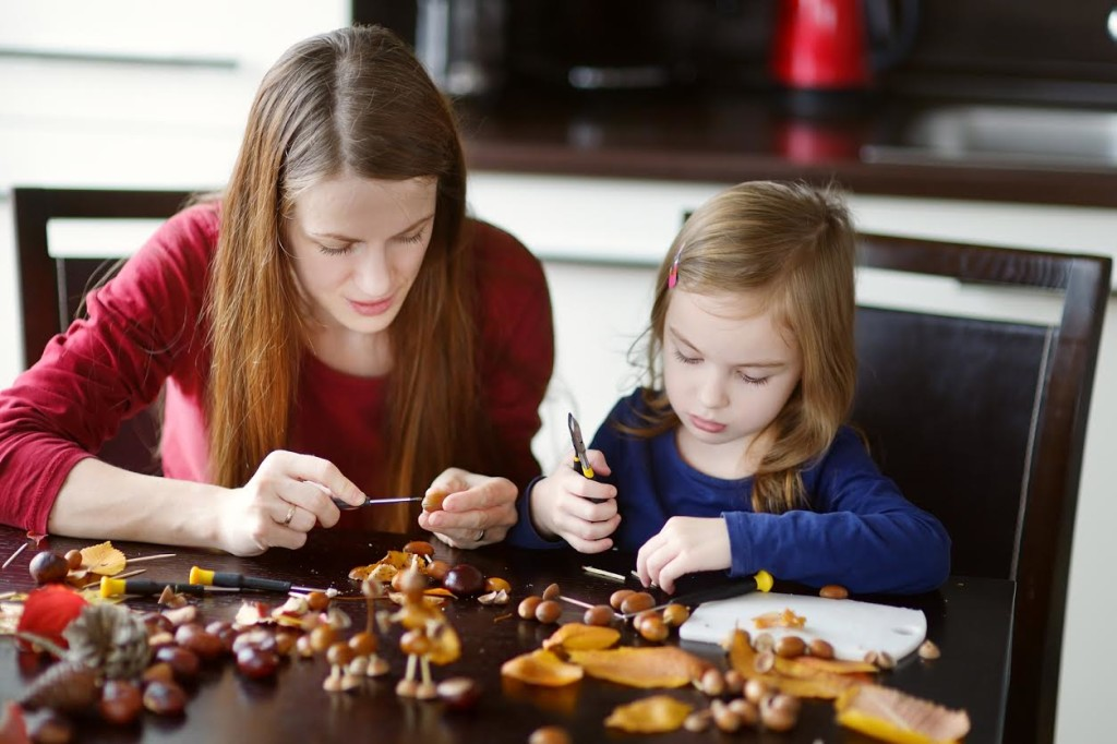 Mother and her kid making chestnuts creatures together