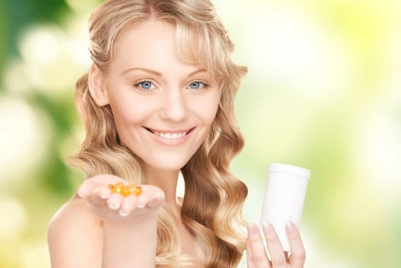 Smiling Woman Holding Omega-3 Capsules