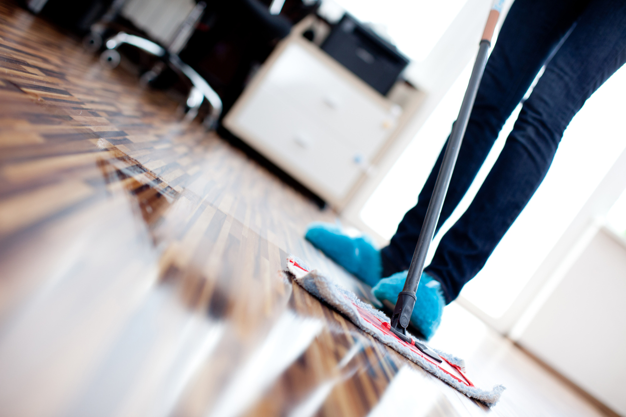 Harwood floors being cleaned with a mop and a proper hardwood cleaning solution.