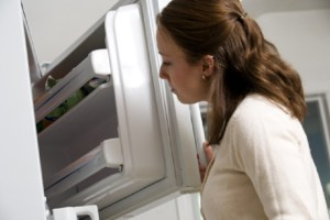Woman acutely aware of amount of ice cream in freezer
