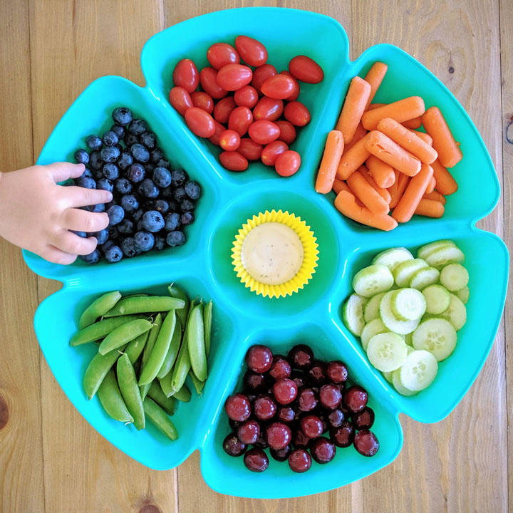This simple dollar store snack tray is perfect for an after school snack for the kids. It's filled with carrots, cucumber, grapes, peas, blueberries, and tomato...but you can put whatever you want in it.