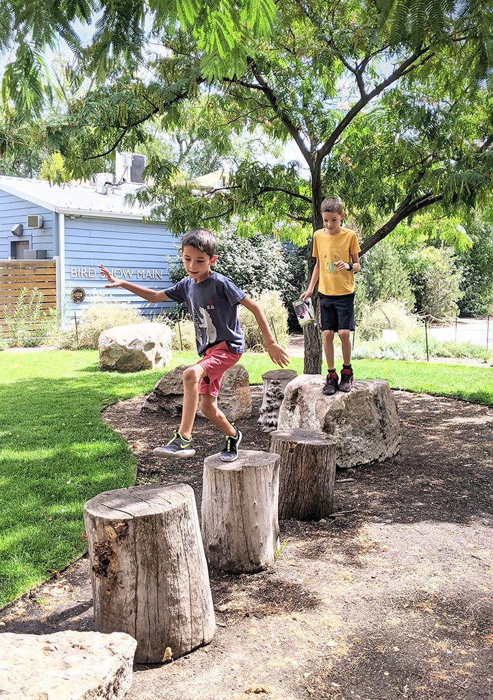Boys hopping across logs during a Fun Friday Family Activity