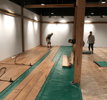 Employees installing prefinished flooring in Denver showroom