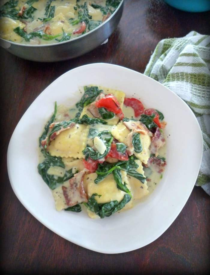 You'll love this simple, easy to make Creamy Ravioli with Bacon Spinach and Red Roasted Peppers , made with quality cheese stuffed Ravioli, fresh organic spinach, Hickory smoked thick sliced bacon, freshly roasted red sweet bell peppers, shallots, all covered in a thick, rich, creamy, homemade four cheese Alfredosauce.