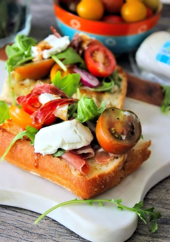 Treat your guests to a delicious flavorful lunch of Goat Cheese Tomatoes and Prosciutto on Ciabatta Bread in a snap! How can you go wrong with wonderful flavors like Goat Cheese, Heirloom vine-ripened tomatoes, Prosciutto, peppery Arugula, fresh basil, garlic, and warm balsamic? Its a little slice of heaven if you ask me.