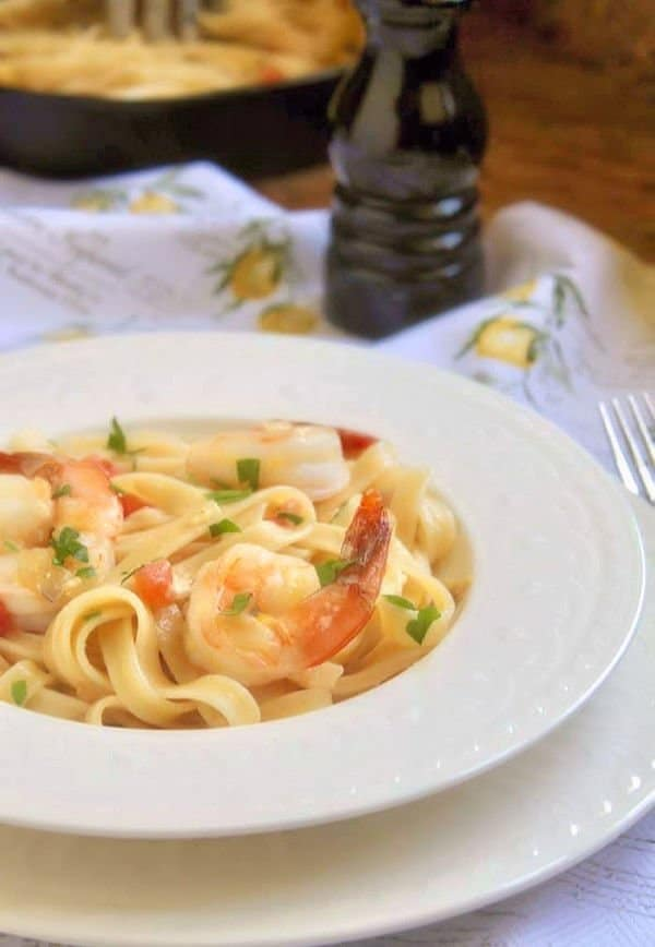 This deliciously creamy shrimp fettuccine with a light cream sauce and tomatoes is perfect for a simple weeknight meal. For the company, just arrange the shrimp on the plate with some parsley, and it's a show stopper of a dish. - Christina's Cucina