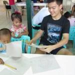 Jane showing her artwork to Joshua Emmanuel Tan.