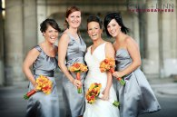 Bridesmaids in grey dresses with orange bouquets
