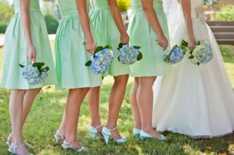 Bridesmaids in mint dresses with blue hydrangea bouquets