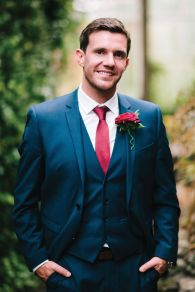 Groom in a navy suit with red tie {via weddingideasmag.com}