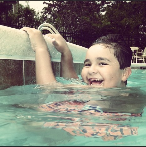 son happily playing in the pool