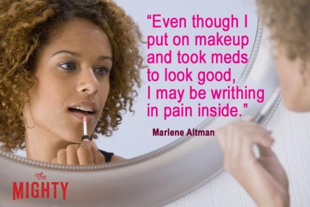 Woman applying lip gloss in mirror