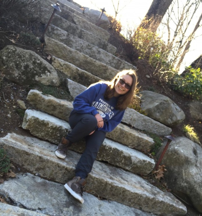 Teen girl sitting on outdoor, stone stairs.