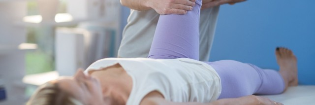 male physical therapist helping a woman bend her knee in a clinic