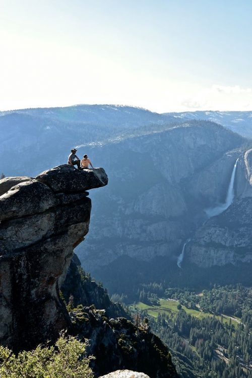 two people sitting on a cliff at yosemite