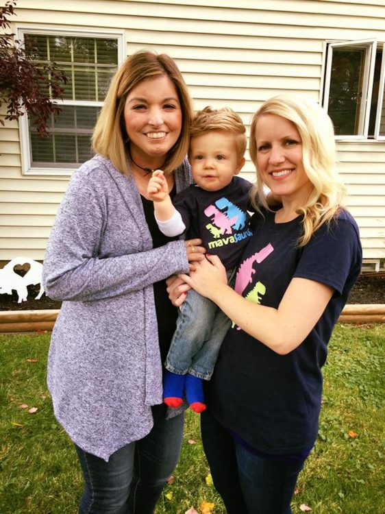 two women holding a boy on his first birthday