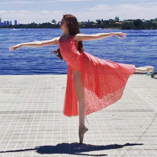girl wearing pink dress and ballet shoes standing on one foot in ballet pose