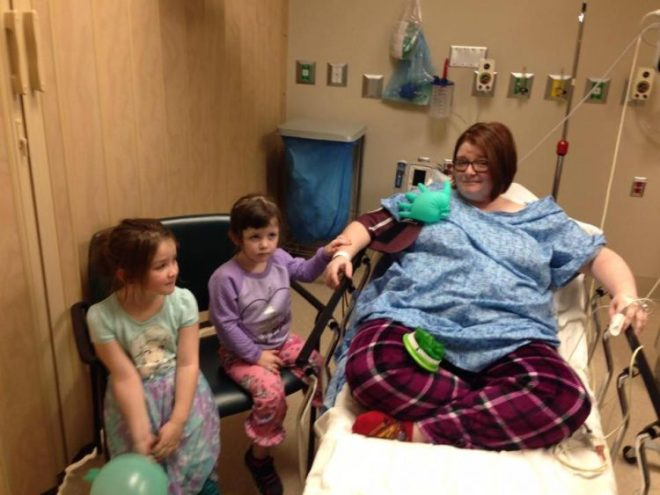 woman sitting on hospital bed with two young kids on chairs next to her