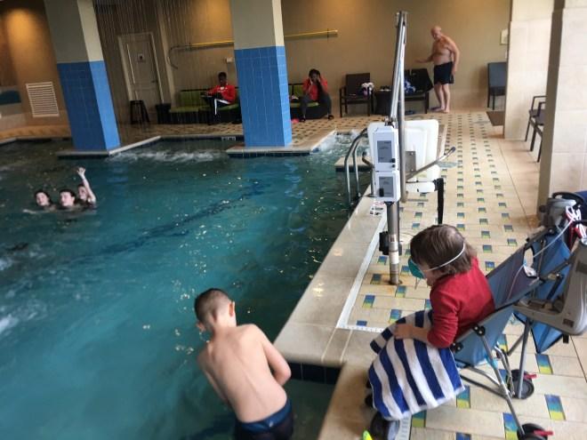 boy in wheelchair playing near a pool