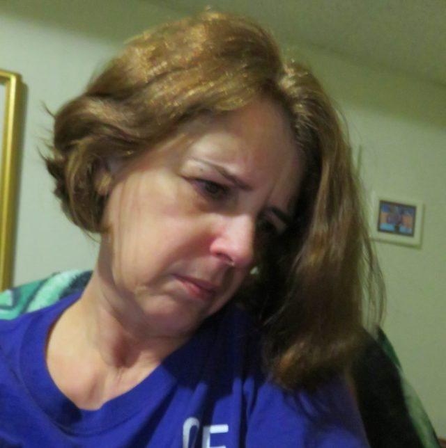 woman wearing a purple shirt and looking down to her left