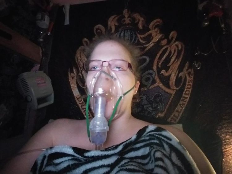 woman lying down with a zebra blanket across her. she has an oxygen mask strapped to her face