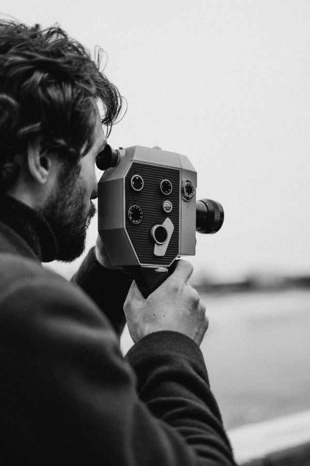 man in long sleeve capturing photo