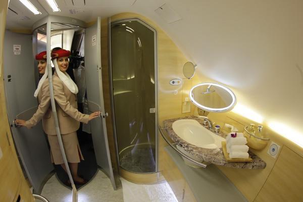 A stewardess poses inside a Emirates A380 bathroom.
