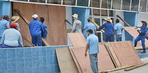 Arriba, septiembre de 2016, trabajadores en Yaguajay, Cuba, se preparan para protegerse de ciclón Irma. Abajo, Skylar Fahlamn trata de salvar sola su casa asediada por los incendios en Ventura, California. En Cuba revolucionaria el lema es 'nadie queda abandonado'. En el capitalismo, es cada quien por su propia cuenta.