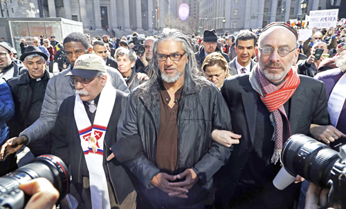 Ravi Ragbir, center, executive director of the New Sanctuary Coalition, walks with hundreds of supporters as he arrives for his annual check-in with Immigration and Customs Enforcement, Thursday, March 9, 2017, in New York.