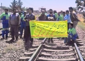 "Track workers near Nayshabour, Aug. 7 protest effects of Iranian rulers' counterrevolutionary wars. Banner says, ""We have not been paid wages for several months. We have no job security. We have no future. We have no honor. We have no bread. We have no social benefits."""