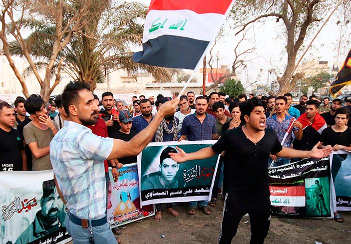Manifestantes en Basora el 12 de septiembre con banderas de Iraq y fotos de muertos en protestas anteriores exigen agua, electricidad y empleos y la no injerencia iraní en el país.