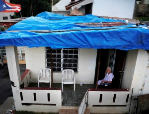 Lucila Cabrera, 86, sits on porch of her house near Barceloneta, Puerto Rico, still covered with plastic tarp. One year after Hurricane Maria, tens of thousands of homes still have not gotten funds or help to build a new roof. FEMA has denied one third of requests for aid.