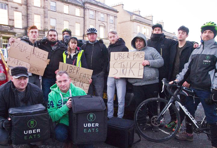 Couriers from Uber Eats in Edinburgh, Scotland, on strike in January against long hours and low pay. App-based bosses and taxi companies profit in pitting drivers against each other.