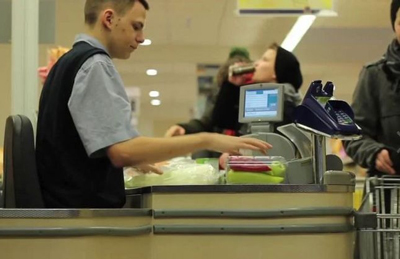 Cashier in Europe sits down while working at supermarket.