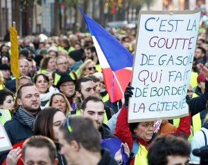 "Over 250,000 demonstrators rallied throughout France Nov. 17 in an explosion of anger against rising gas prices. Sign says new taxes are ""the drop of diesel that overflows the gas tank."""