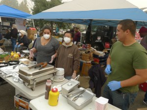 Volunteers wearing masks to keep out smoky air serve food to fire survivors at Walmart encampment Nov. 15. Hundreds of workers are volunteering in face of government inaction.