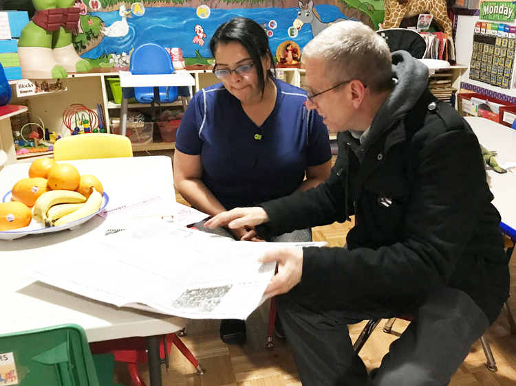 SWP member Seth Galinsky shows Ligia Rivera the Militant at the day care center she runs out of her home in the Bronx, Nov. 11. Many Uber drivers leave their children with her during the crazy hours that they work, she said. She bought a Militant subscription, as well as Malcolm X, Black Liberation, and the Road to Workers Power and The Clintons' Anti-Working-Class Record.
