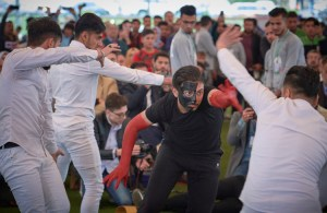 Mime performance by Mosul University students Nov. 30 acts out recent history. Dancers in white defeat Islamic State fighters in black, return a painting to view and a musician plays his flute to cheers of the crowd.