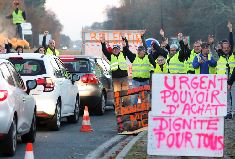 """Yellow vests,"" working people from small towns, countryside, win support for their struggle in Cis-sac-Medoc, France, Dec. 5. Sign at right says ""Urgent, purchasing power, dignity for all."""