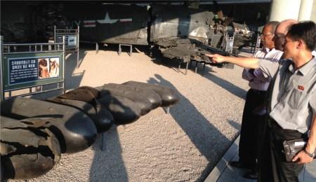 Restos de bombas y armas norteamericanas en el Museo de la Guerra de Corea en Pyongyang. Desde la izq.: James Harris y Steve Clark, miembros de la delegación del Partido Socialista de los Trabajadores en Pyongyang para celebrar el aniversario del cese al fuego de 1953, recorren exhibiciones con guía. Harris fue candidato presidencial del PST en EE.UU. en 2012.